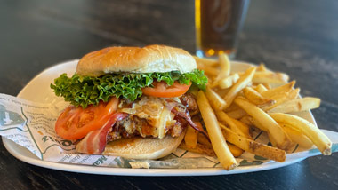 chicken sandwich with bacon, cheese, fried onions, lettuce & tomato and fries
